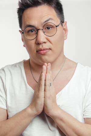 Asian man in t-shirt, holding hands in pray, begging for help or asking apology Фото со стока