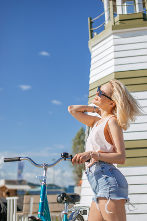 Woman leaning on the bicycle while standing near observation deck on the beach