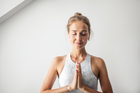 Young attractive Yoga teacher female greeting at the begining of practicing yoga Stock Photo