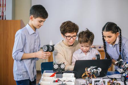 Des enfants heureux apprennent la programmation à l'aide d'ordinateurs portables dans des classes parascolaires