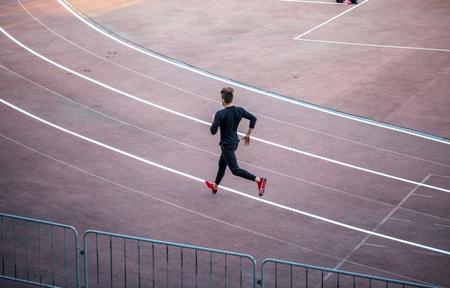 Top view Athlete running on running track. Runner sprinting on red running track in stadium