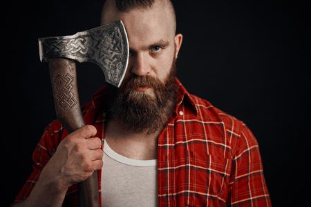 man with mustache is holding a battle axe cover his eye and looking on camera on black background Reklamní fotografie