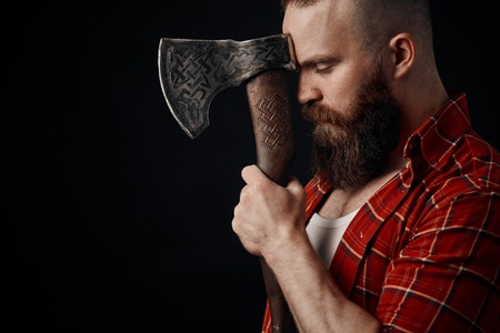 lumberjack. Confident bearded man attached to forehead axe Stock Photo