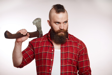 mohawk bearded male holds axe on his shoulder on white background Фото со стока
