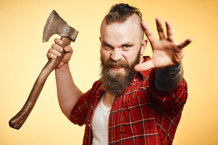 agressive lumberjack. bearded man swinging with axe