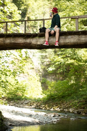 Traveler sits on wooden bridge and uses smartphone to see map for navigating.