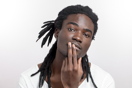 Thinking man with two fingers near mouth. male looking at camera Stockfoto