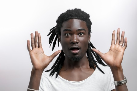 shocked African American man wearing white T-shirt looking at camera in surprise