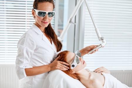 Woman getting laser face treatment in medical center, skin rejuvenation concept