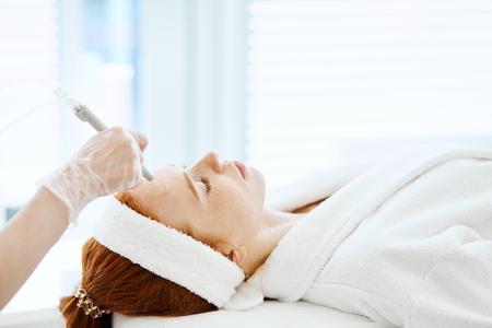 Frau, die Gesichtspeelingverfahren im Schönheitszentrum erhält. Gesichtsgas-Flüssigkeitspeeling