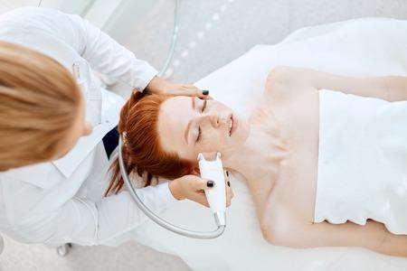 Mujer que consigue el levantamiento de rf en un salón de belleza. Tecnologías modernas en cosmetología.