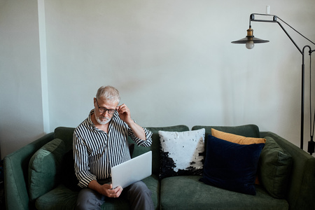 mature bearded man working from home with laptop. sitting at desk near window Stock Photo