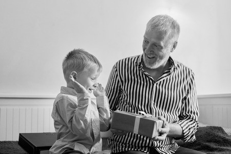 generation. grandfather and grandson with gift box sitting on couch at home