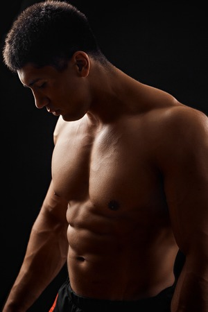 gorgeous tanned body in a dark room