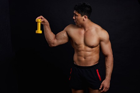 man is holding dumbbell and looking at it with irony, sceptical expression