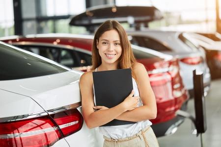 Female seller holding black folder looking at camera at car dealership.