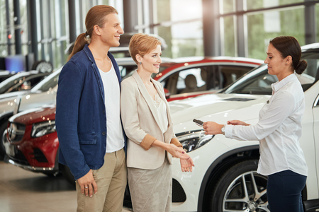 Happy young couple receiving car key from a salesman at the car dealership.
