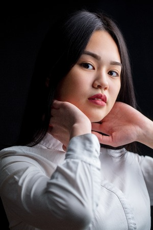 Asian young woman in white over black background. Black and Whit