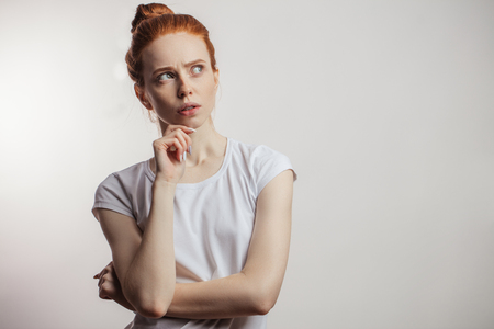Redhaired woman looking up with pensive expression isolated on white background.