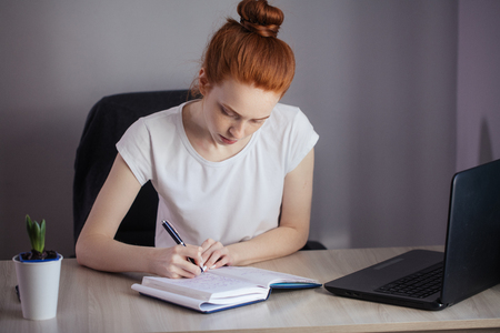 Portrait of redhaired young woman with laptop sitting at the table