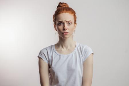 Chica pelirroja con moño y pecas aislado sobre fondo gris