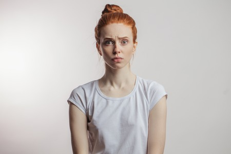 Redhead girl with hair bun and freckles isolated over grey background