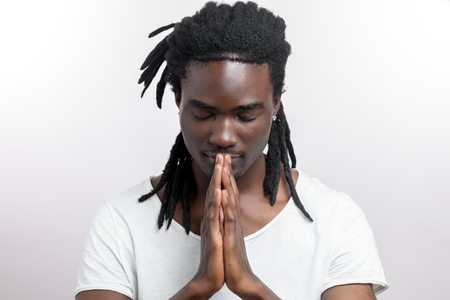 Close up of black man with dreadlocks praying on white background