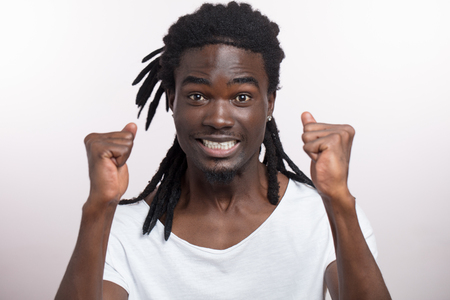 handsome happy young african man with dreadlocks on white background Stock Photo