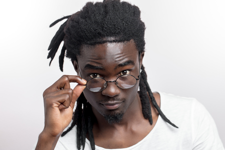 Afro American man with dreadlocks and glasses is looking at camera