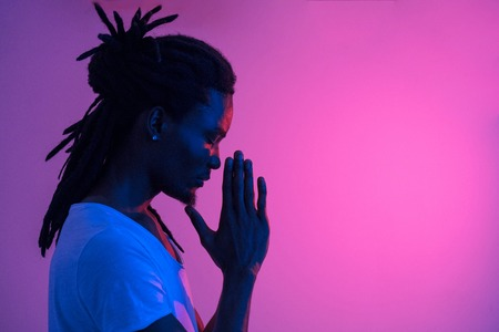 Close up of black man with dreadlocks praying on purple background Stock fotó