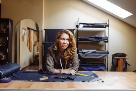 Portrait of pleasant adult dressmaker woman at tailors workshop