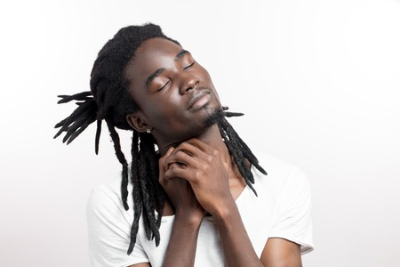 Thinking or dreaming african man with dreadlocks on white background