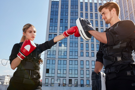 two young people training with boxing gloves on the street
