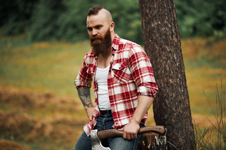 Lumberjack sitting in forest resting after hard work