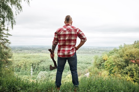 Rear view of lumberjack in forest holding an axe on his shoulder Stock Photo