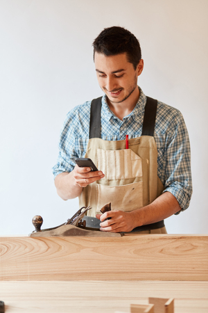 carpenter working with wood using plane against white wall in studio. Stock fotó