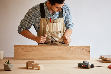 carpenter working with wood using plane against white wall in studio.