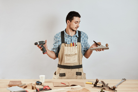 Emotional male carpenter in workwear and apron having confused puzzled look Foto de archivo