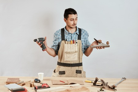 Emotional male carpenter in workwear and apron having confused puzzled look Standard-Bild