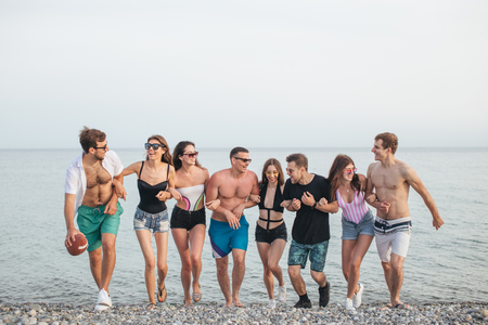 Group of Friends Walking at Beach, having fun, womans piggyback on mans, funny vacation Stockfoto