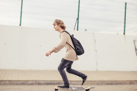 boy riding longboard on boardwalk, warm summer time 版權商用圖片
