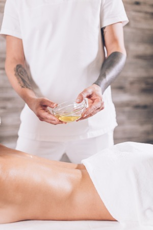 man is going to massage females body with oil