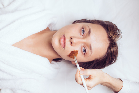 gorgeous good looking girl lying on the bed and having a face mask Archivio Fotografico