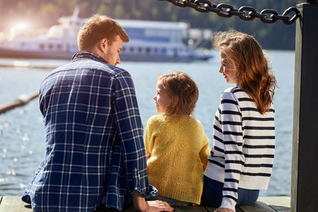rear view of family sit on pier in autumn day. Fall family portrait