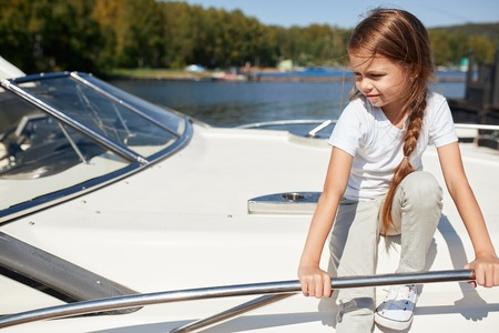 girl on boat deck sails on summer day