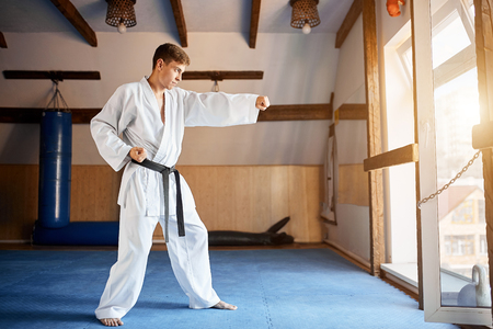 Man in white kimono with black belt training karate in gym