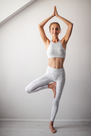 Woman working out indoors, standing in Tree Pose on window sell