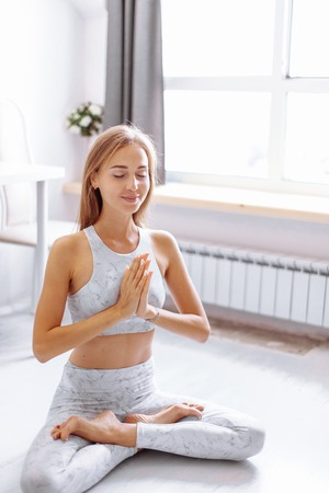 Young woman practicing Lotus pose on meditation session, isolated in studio