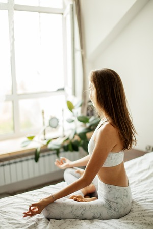 Woman meditating in her bed, rear view
