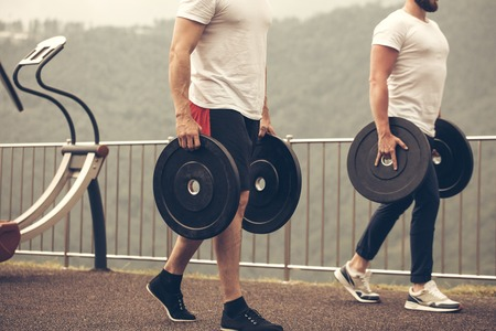 Caucasian muscular men with weight plates preparing to outdoor workout. Stock Photo